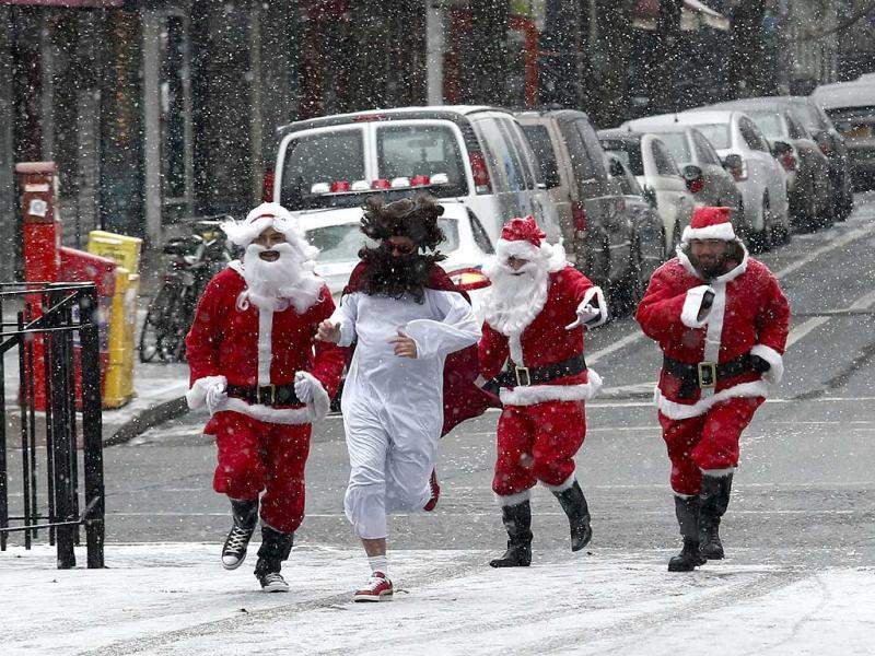 Three revelers dressed as Santa Claus run in a park during the SantaCon event in New York. (Reuters)