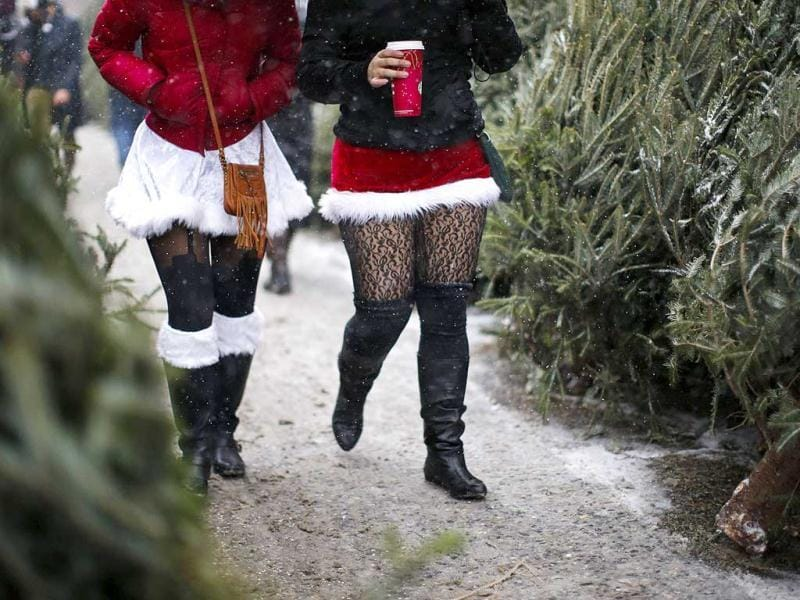 Revelers dressed as Santa Claus walk in the snow during SantaCon in New York. (Reuters)