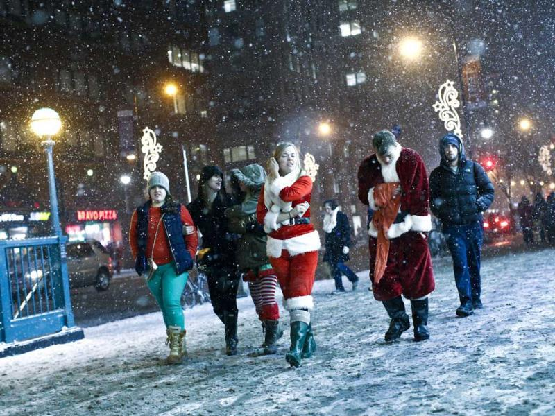 Revelers dressed as Santa Claus walk during snowfall for the annual SantaCon event in New York. (Reuters)