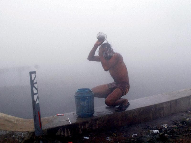 A youth bathing on a foggy morning in Allahabad. (PTI)
