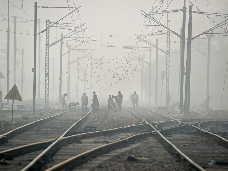 Labourers work on railway tracks on a foggy morning in New Delhi. (AFP)