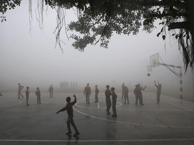 Schoolchildren play on a basketball court surrounded by morning fog in New Delhi. (AP)