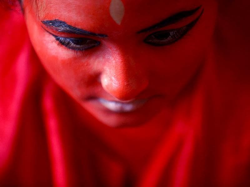 A woman paints her face red. (Reuters Photo)