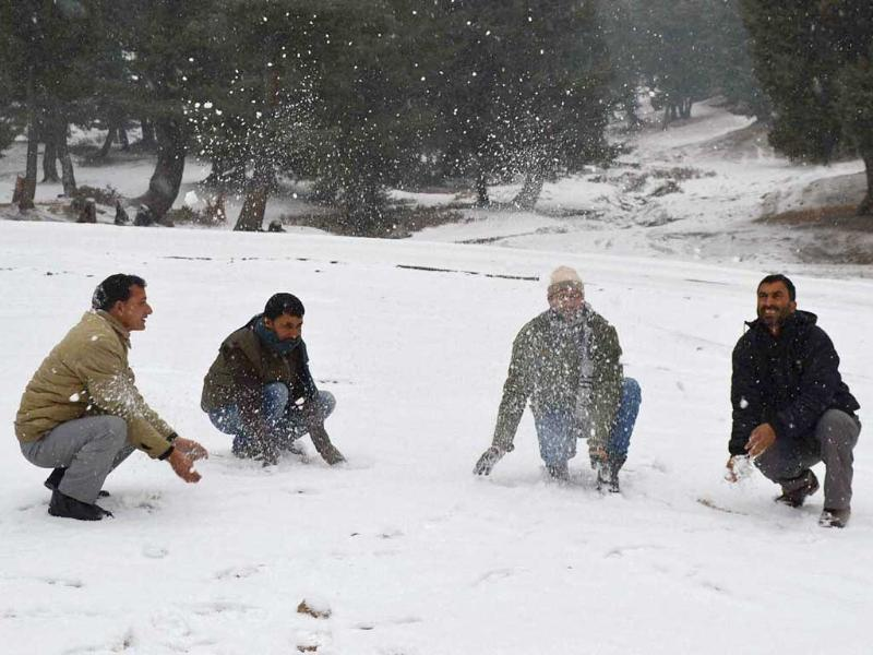 Tourists play with snow near Mughal Road during snowfall in Shopian district. (PTI)