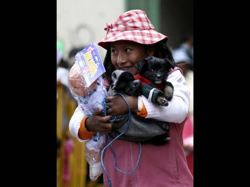 A girl holds a toy and a dog after a Christmas celebration organised by a catholic organisation that donates free toys in La Paz. (Reuters)