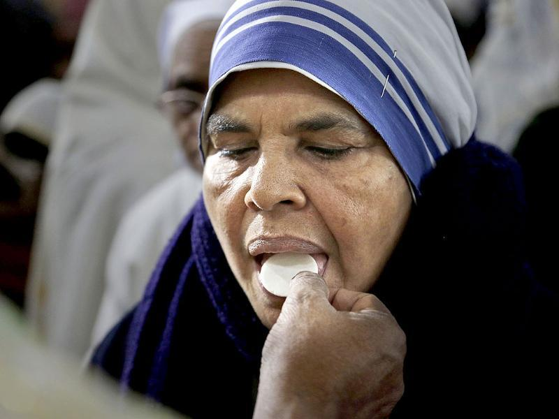 An Indian nun receives a communion wafer from a priest during Christmas in a church in Gauhati, India. (AP Photo)