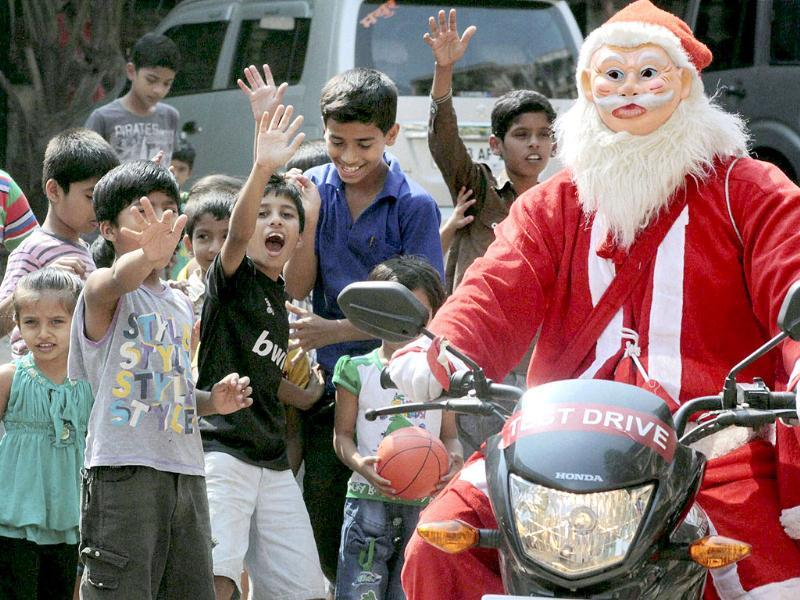 Santa Claus gives the raindeers a rest and takes transport of a more modern nature in Navi Mumbai. (PTI Photo)