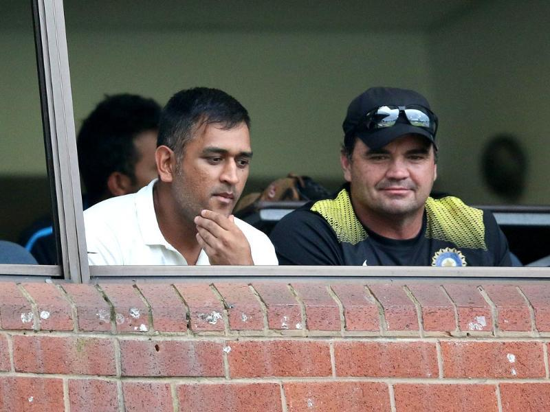 Captain Mahendra Singh Dhoni watches the match from the changing room during a break for bad light on the first day of the second Test match between India and South Africa at the Sahara Stadium Kingsmead in Durban . (AFP photo)