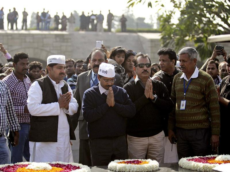 Aam Aadmi Party convener Arvind Kejriwal (C) pays respect at Raj Ghat after being sworn in as the chief minister of Delhi. (AP Photo)
