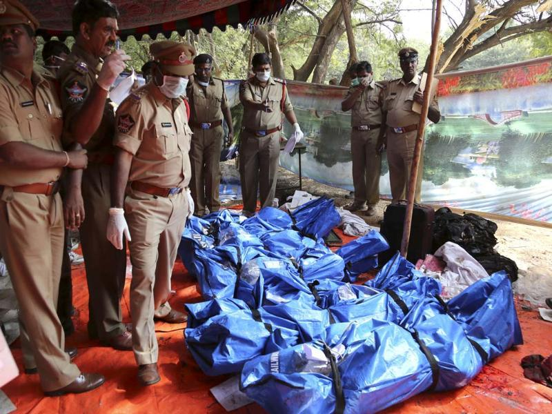 Police officers stand by the bodies of passengers killed in the train accident at Kothacheruvu, about 155 kilometers north of Bangalore. (AP)