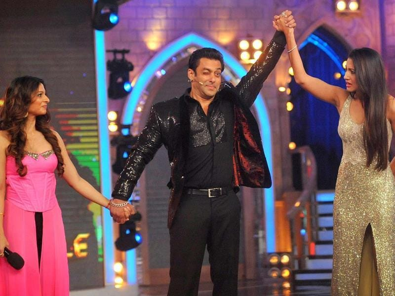 Salman Khan raises Gauhar Khan's hand to declare her a winner while runner-up Tanisha Mukherjee looks on during Bigg Boss Season 7 finale. AFP
