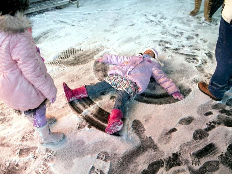 A child makes a snow angel in Times Square in New York. The snow storm is expected to bring snow, stiff winds and punishing cold into the Northeast.(AP photo)