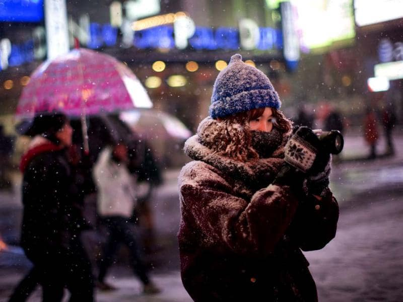 A pedestrian takes a photograph under falling snow in Times Square in New York. (AP photo)
