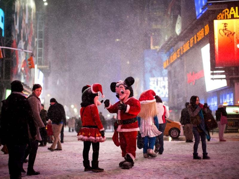 Two people dressed as Disney characters talk under falling snow in Times Square in New York. (AP photo)