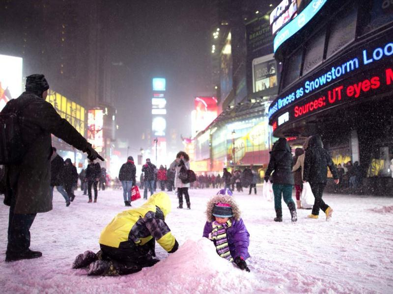 Children make a snow pile in Times Square, during a snowstorm in New York. New York and New Jersey declared a state of emergency and urged residents to stay indoors as a major storm, called Hercules. (AP photo)
