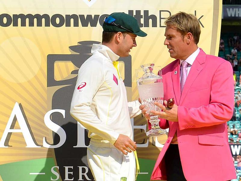 Captain Michael Clarke (L) receives the Ashes Test series trophy from Australia's former spin bowler Shane Warne at the Sydney Cricket Ground. (AFP Photo)