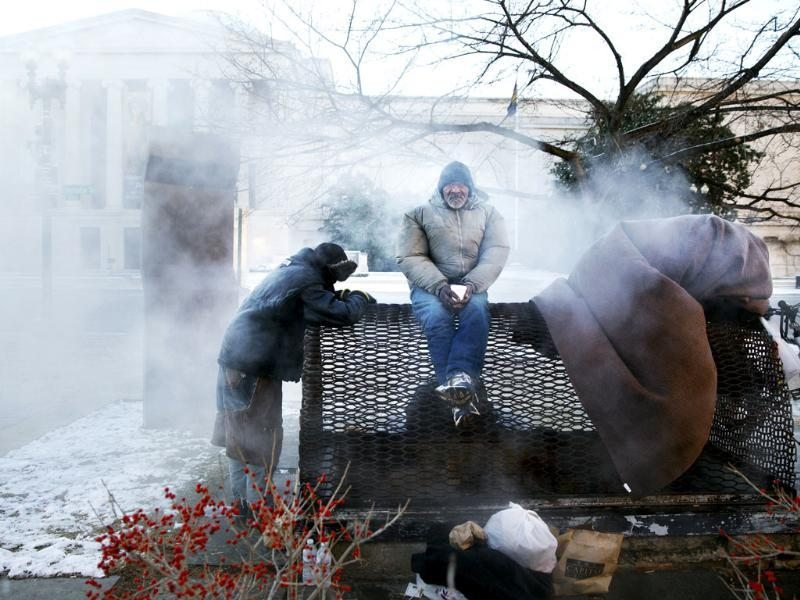 Four homeless men warm themselves on a steam grate by the Federal Trade Commission, blocks from the Capitol, during frigid temperatures in Washington (AP Photo)
