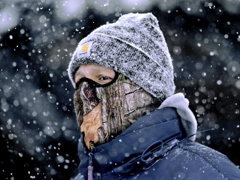 A man wears a face mask and heavy clothes while walking through downtown Springfield, Ill., in blowing and falling snow as a strong winter storm moves through the Midwest. (AP Photo)