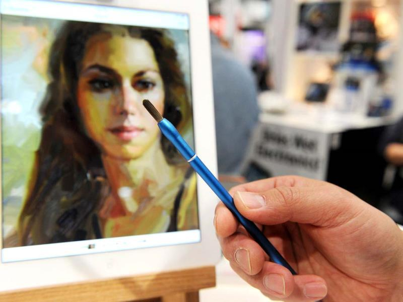 A NomadBrush Flex paintbrush stylus is displayed in front of an iPad 'oil' painting by artist Rick Graham at the 2014 International CES in Las Vegas, Nevada. (AFP Photo)