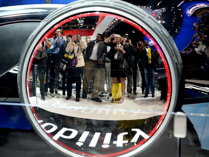 Attendees are reflected in the wheel of the Toyota FV2 future mobility concept car at the 2014 International CES in Las Vegas, Nevada. (AFP Photo)