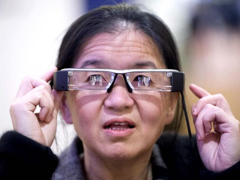 An attendee tries the Epson Moverio BT-200 smart glasses, at the 2014 International CES in Las Vegas, Nevada. The Moverio BT-200 projects two identical 16:9 images onto the lens-based screens, generating a semi-transparent picture to fall within the user's field of vision. (AFP Photo)