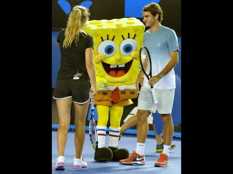 Roger Federer of Switzerland (R) and Victoria Azarenka of Belarus (L) team up with cartoon character Sponge Bob during the Kids Day exhibition match ahead of the Australian Open. (AFP Photo)