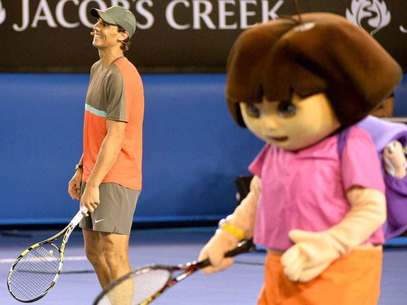 Rafael Nadal of Spain (L) gestures as he is joined on court by cartoon character Dora the Explorer during the Kids Day exhibition match ahead of the Australian Open tennis tournament. (AFP Photo)