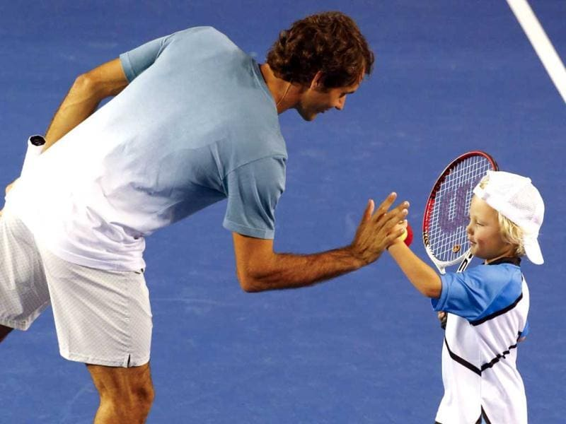 Roger Federer of Switzerland high fives Cruz Hewitt, the son of Lleyton Hewitt of Australia, during the Kids Tennis Day before the Australian Open. (Reuters Photo)