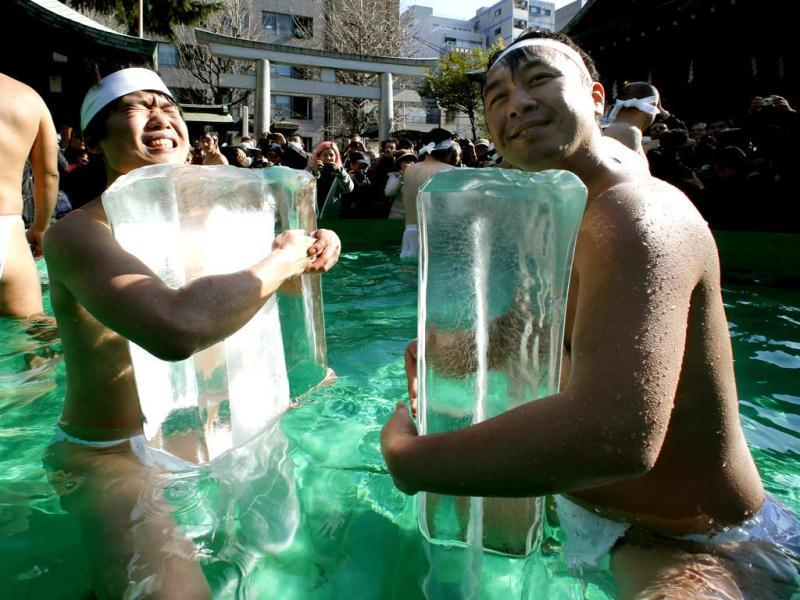 Japanese physical fitness enthusiasts hold blocks of ice while standing in cold water at Teppozu Inari Shinto shrine during a winter ritual to keep themselves fit in Tokyo. (AP)