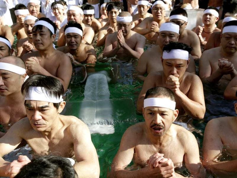 Fitness buffs pray while dipping in cold water at the shrine during to display their perseverance. (AP)