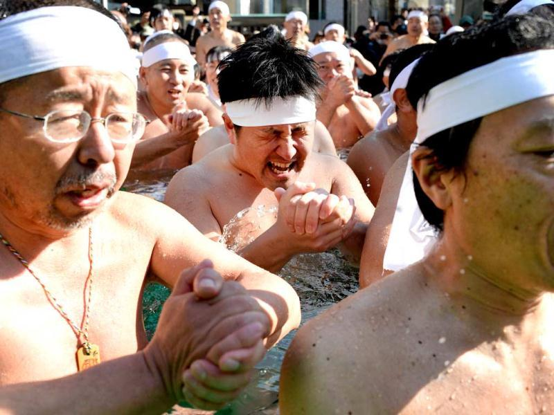 People pray as they soak in cold water to purify their bodies and souls during a New Years event at the Teppozu-inari Shrine in Tokyo. (AFP)