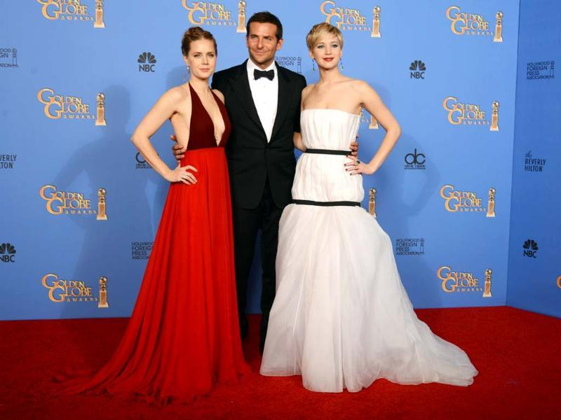Both Amy Adams, in her sleeveless burgundy dress, and Jennifer Lawrence, in her white dress covered with two black bands (why?), failed to fire fashion critics' imagination. Bradley Cooper poses with the two beauties.