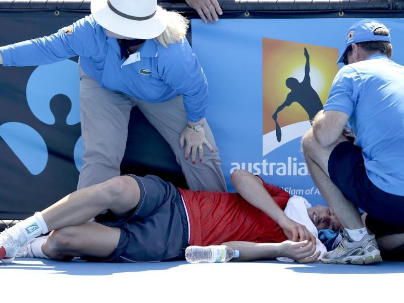 Frank Dancevic of Canada lies on the court after collapsing during his first round match against Benoit Paire of France as temperatures topped at 43 C (108 F) at the Australian Open in Melbourne. (AP Photo)