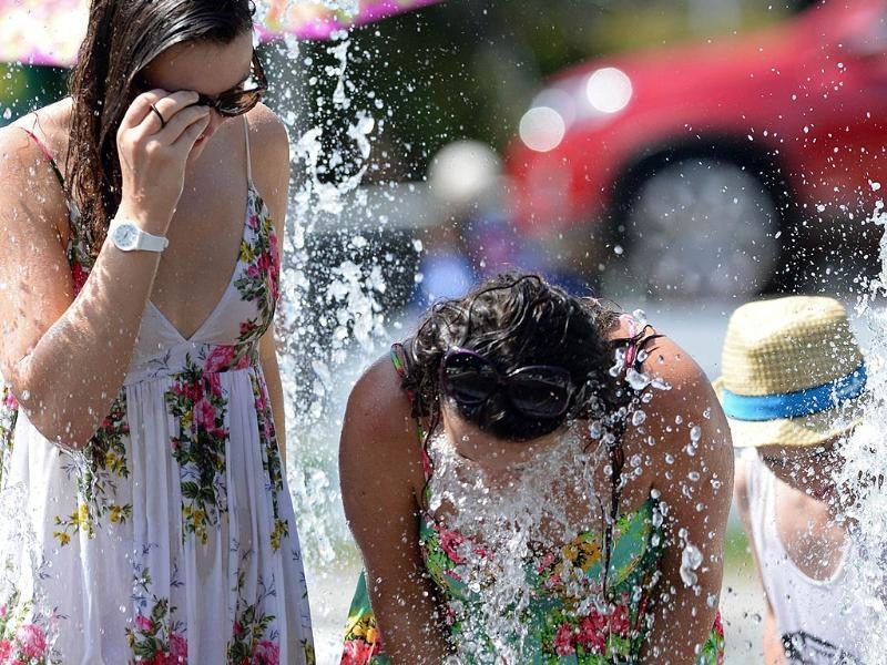 Spectators cool down in a fountain during the hot weather on day two of the 2014 Australian Open in Melbourne. (AFP Photo)
