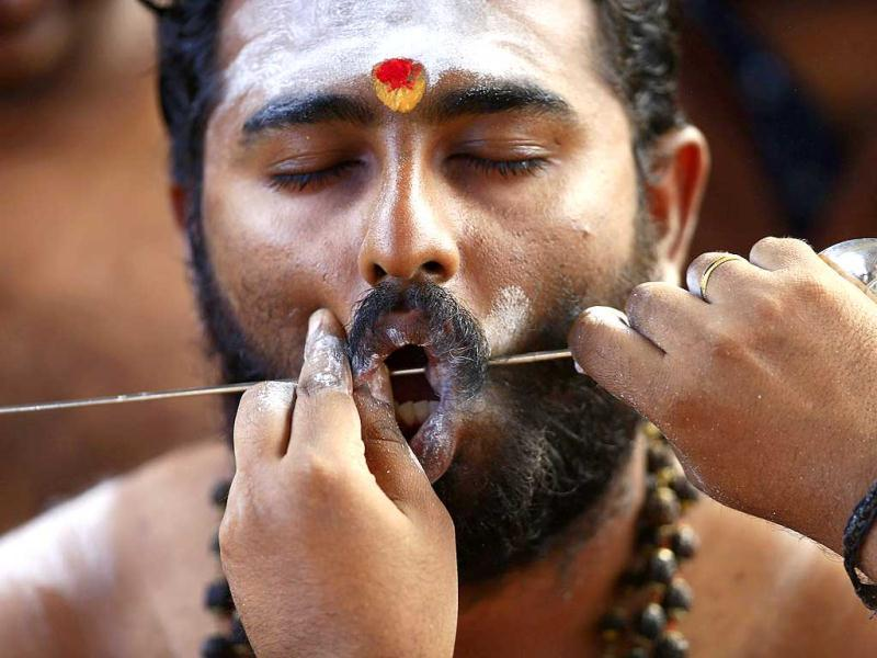 A Malaysian Hindu devotee has his cheeks pierced with a skewer, before a pilgrimage to the sacred Batu Caves Temple during Thaipusam festival outside Kuala Lumpur. (Reuters)