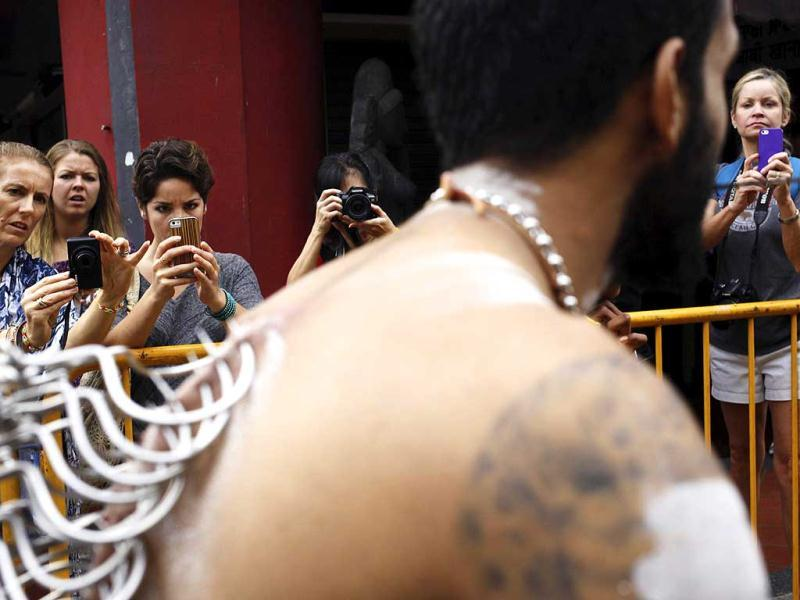 Bystanders take photos as a devotee pulls a chariot with hooks pierced into his back during the Thaipusam festival in Singapore. (Reuters)