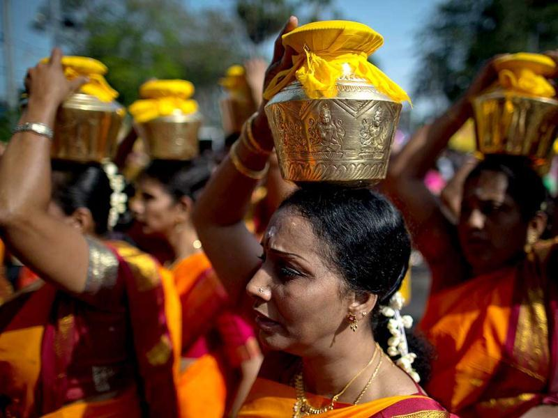 Hindu devotees carry milk pots on their heads for offering as they walk toward the Murugan temple during the colourful annual Thaipusam festival, one of the world's most extreme displays of religious devotion, in Malaysia. (AFP)