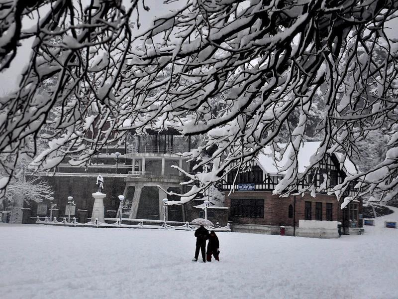 A couple walk down a snow covered road at Ridge in Shimla. (Santosh Rawat/HT Photo)