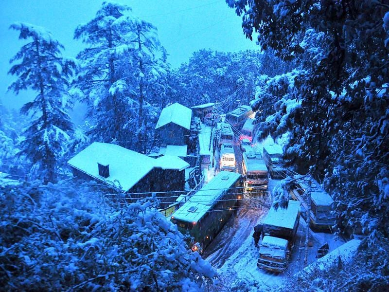 Vehicles move at snail's pace during heavy snow fall in Shimla. (Santosh Rawat/HT Photo)