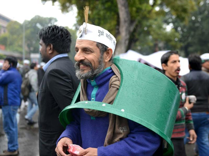 A supporter of Delhi CM Arvind Kejriwal wears a trash bin top over his head on a rainy morning during a dharna in New Delhi. (AFP photo)