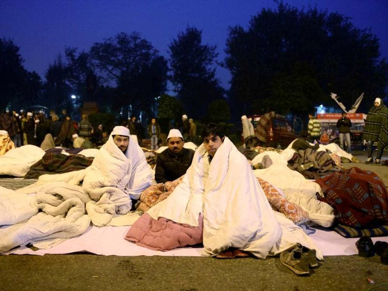 A supporter of Delhi CM Arvind Kejriwal spent the night on the street during a dharna in New Delhi. (AFP photo)