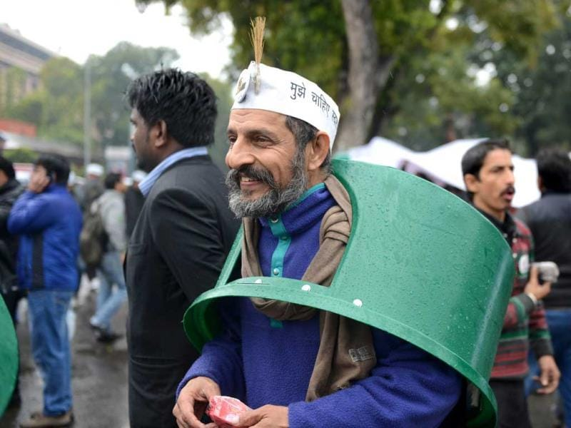 A supporter of New Delhi chief minister Arvind Kejriwal wears a trash bin top over his head on a rainy morning during a sit-in protest in New Delhi. (AFP Photo)