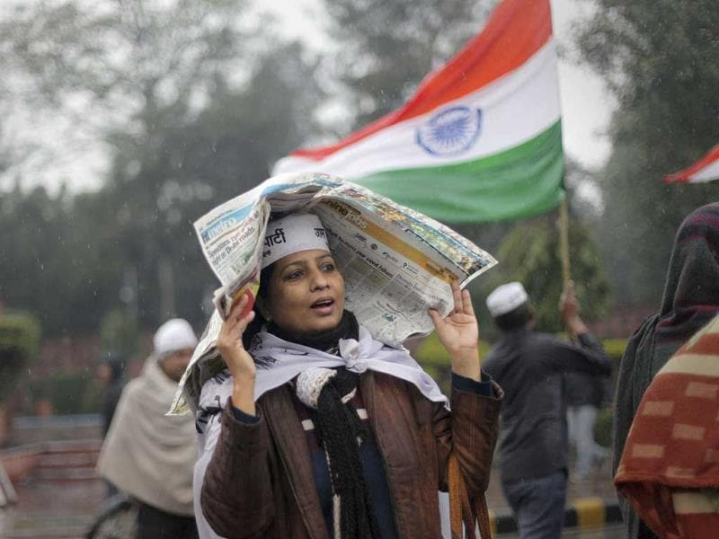 A supporter of New Delhi chief minister Arvind Kejriwal uses a newspaper to protect herself from the rain during a demonstration against the police in New Delhi. (AP Photo)