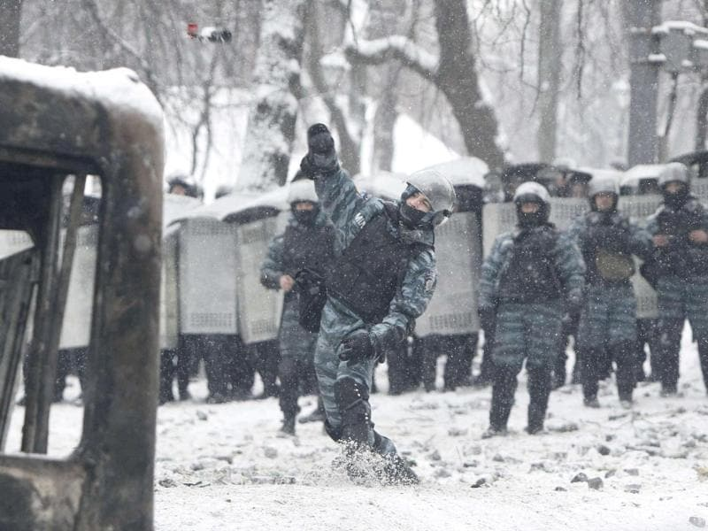 A Ukrainian riot police officer throws a bottle during clashes with pro-European protesters in Kiev. (Reuters Photo)