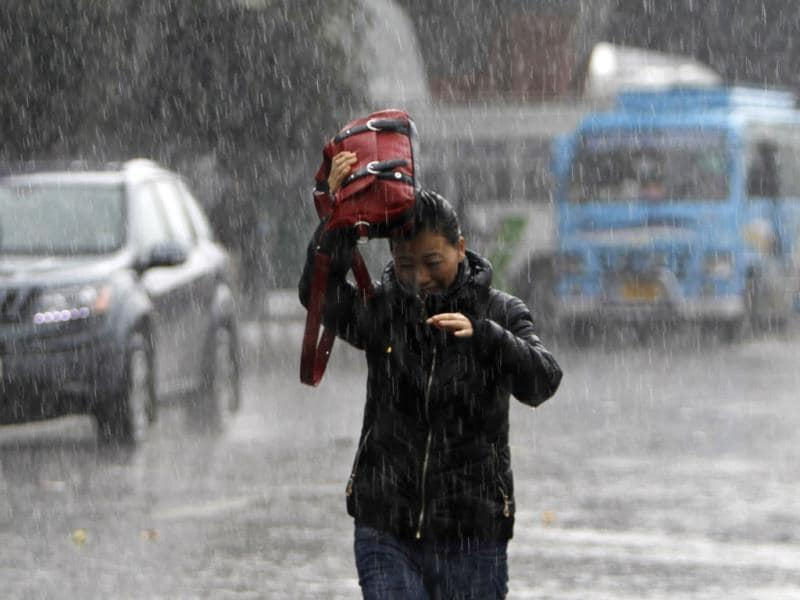 A woman walks through a street as it rains in Jammu. Heavy snowfall threw normal life out of gear in Jammu and Kashmir Wednesday, snapping road and air links between the state and the rest of the country. (AP Photo/Channi Anand)