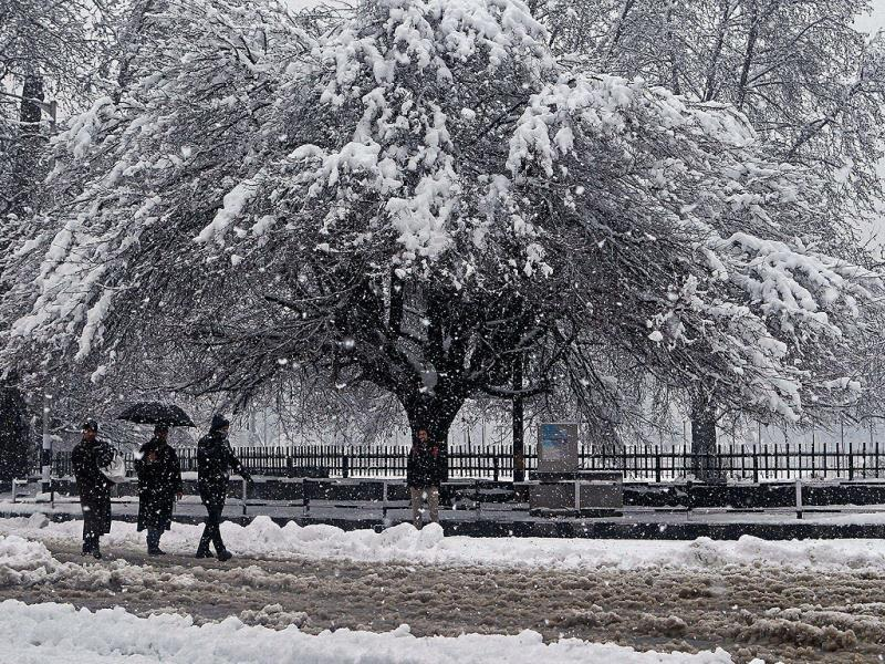 People walk during heavy snowfall in Srinagar. Kashmir valley experienced fresh snowfall prompting authorities to suspend traffic on Srinagar-Jammu national highway and air service. (PTI Photo)
