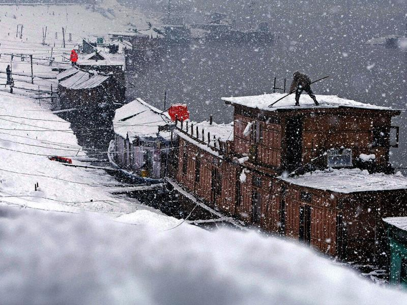 A man clears snow from the roof of his houseboat during heavy snowfall at river Jehlum in Srinagar. Kashmir valley experienced fresh snowfall prompting authorities to suspend traffic on Srinagar-Jammu national highway and air service. (PTI photo)