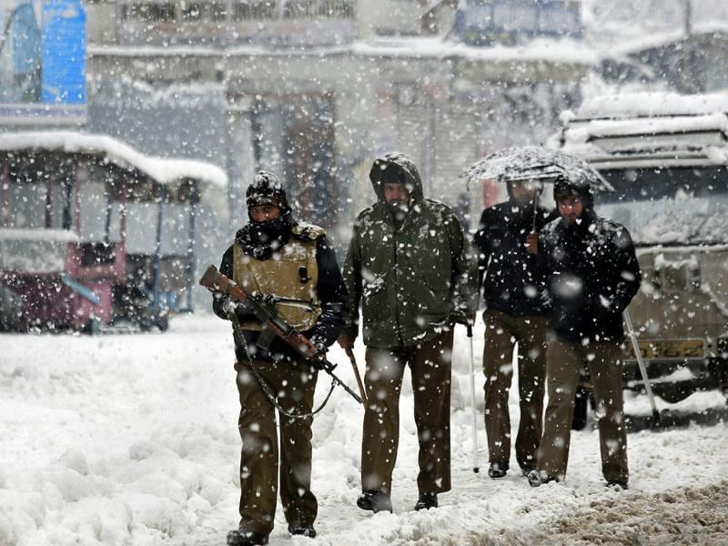 Policemen patrol a snow-covered street in Srinagar. Snowfall in Kashmir has disrupted power supply, air traffic and road traffic between Srinagar and Jammu. (AP Photo)