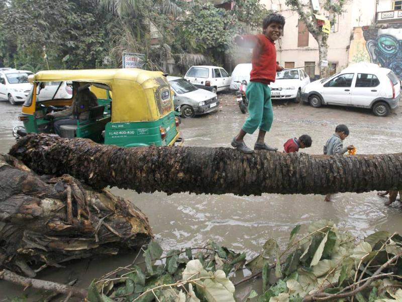 Children playing in waterlogged roads near Khirki Village, in New Delhi (Photo by Raj k Raj/ Hindustan Times)