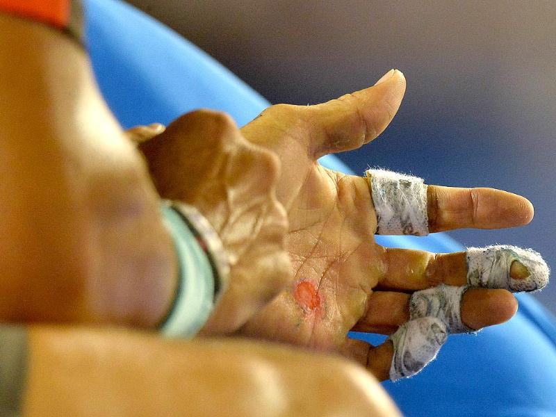 A trainer (background-in blue) helps Rafael Nadal of Spain (L) with his hand as he deals with a blister, during an injury time out against Roger Federer of Switzerland during their men's singles semi-final match at the 2014 Australian Open in Melbourne. (AFP Photo)